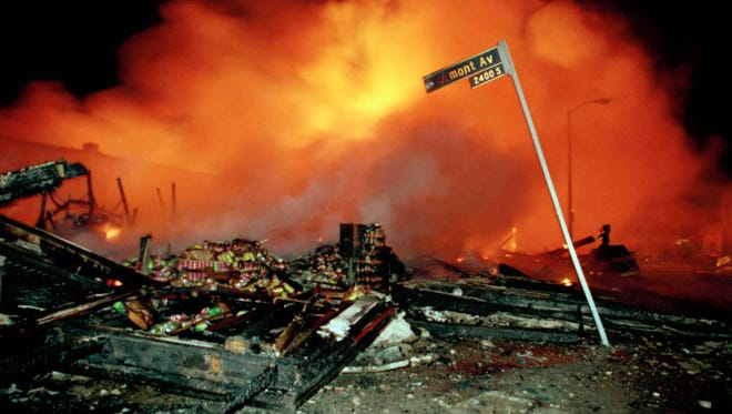 The remains of a commercial building smoulders as another building burns out of control behind the smoke in Los Angeles early Thursday morning, April 30, 1992. Numerous fires were set and stores were looted following the verdict in the Rodney King beating trial. (AP Photo/Douglas C. Pizac).