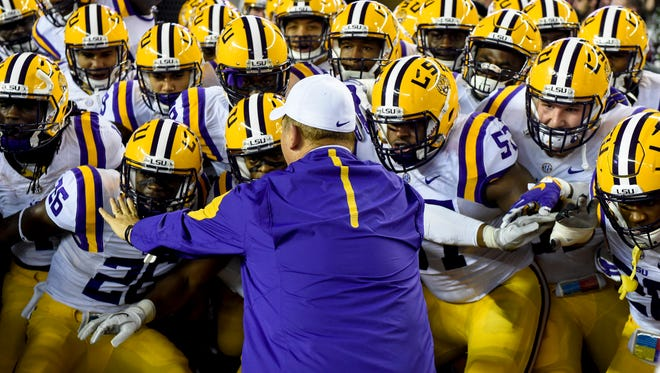 LSU Tigers head coach Les Miles holds back his players prior to taking the field against the Alabama Crimson Tide at Bryant-Denny Stadium.