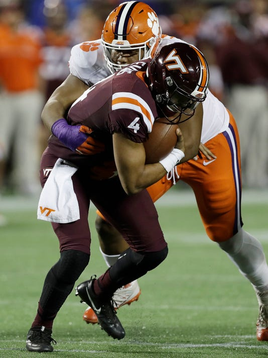 """FILE - In a Saturday, Dec. 3, 2016 file photo, Clemson defensive tackle Dexter Lawrence (90) sacks Virginia Tech quarterback Jerod Evans (4), during the second half of the Atlantic Coast Conference championship NCAA college football game, in Orlando, Fla. Lawrence, the agile freshman who has bedeviled offensive lines, has done the same to defensive opponents as part of the Tigers' """"Jumbo Package."""" (AP Photo/Chris O'Meara, File)"""