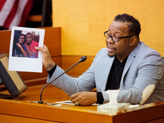 Bobby Brown holds up a picture of his daughter, Bobbi