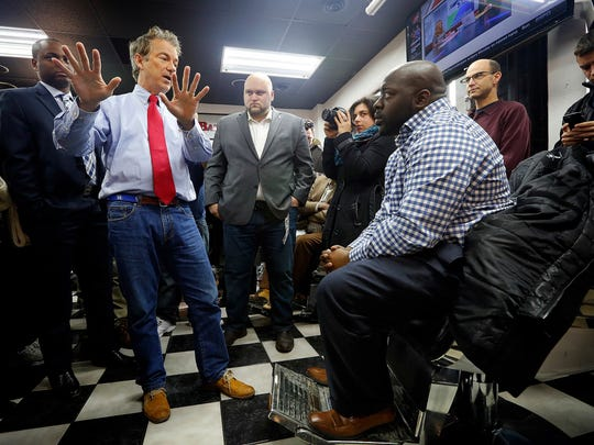 Rob Johnson of Waukee, right, talks with Republican presidential candidate Sen. Rand Paul of Kentucky during a visit to Platinum Kutz barbershop on Jan. 18, 2016.