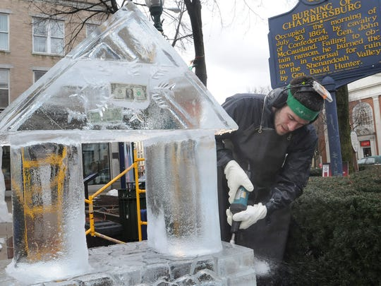 Jared McAlister, of DiMartino Ice Co., carves out a wishing well during the 10th Annual IceFest in 2012.