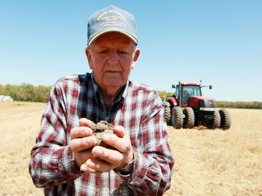 Billy Calloway, shown in this 2012 file photo, holds hard, dry dirt from the field. Before his death last month, he was facing sanction from the Maryland Department of the Environment over nutrient management practices.