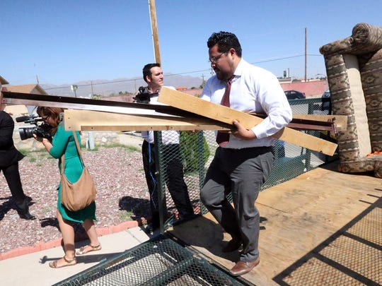 Richard Cerros of the office of U.S. Rep. Beto O'Rourke carries a bed frame into the home of veteran John Rhodes Thursday.
