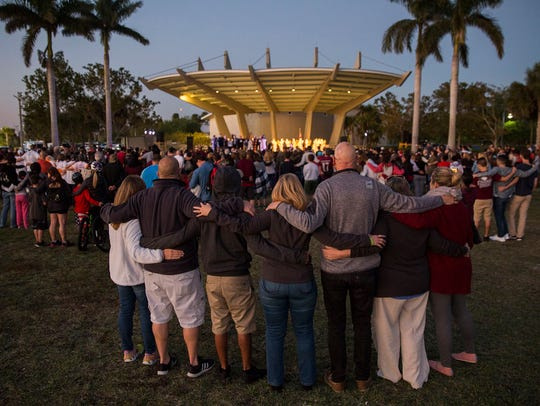 Family, friends and community members embrace during