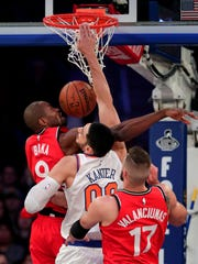 New York Knicks center Enes Kanter (00) dunks against Toronto Raptors forward Serge Ibaka (9) during the first quarter of an NBA basketball game, Wednesday, Nov. 22, 2017, in New York.
