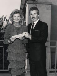 Barbara Sinatra receives a $15,000 check from Ken Rizotto