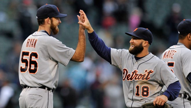 Detroit Tigers pitcher Kyle Ryan, left, celebrates with teammate Tyler Collins after defeating the Chicago White Sox, 6-0, on Sunday, Oct. 4, 2015, in Chicago.