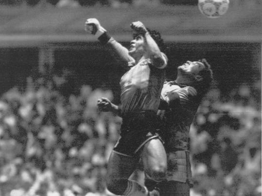 "FILE - In this June 22, 1986 file photo  Argentina's Diego Maradona, left, beats England goalkeeper Peter Shilton to a high ball and scores his first of two goals in a World Cup quarterfinal soccer match, in Mexico City. On this day: This was the day of the ""Hand of God,"" when Maradona used his left fist to knock a ball past England's Shilton. (AP Photo/El Grafico, Buenos Aires, File)"