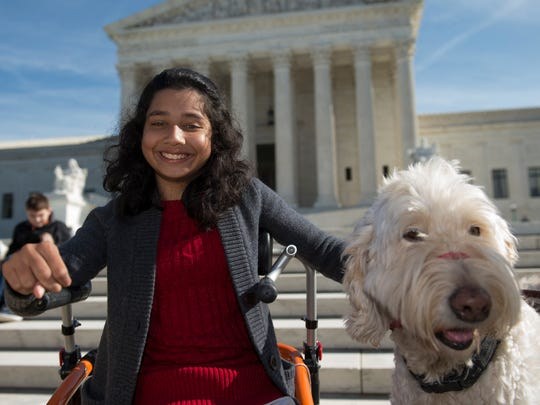 Ehlena Fry sits with her service dog Wonder, while speaking to reporters outside the Supreme Court in Washington on Oct. 31, 2016.