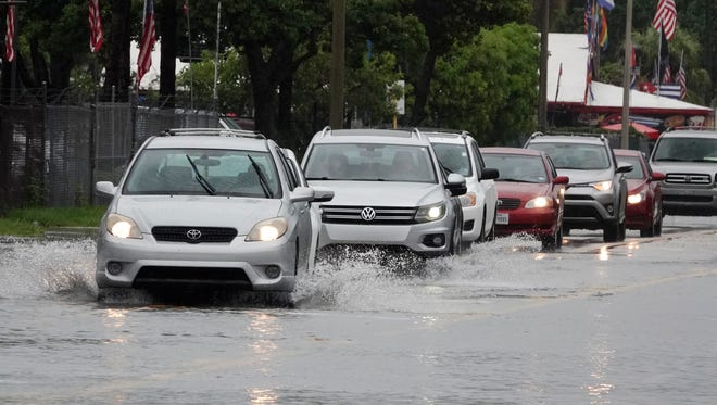 Drivers try to navigate a street where the constant rain has flooded it in Fort Lauderdale, Fla., Sunday, May 20, 2018. More rain is forecast across Florida over the next few days as a tropical disturbance makes its way north into the Gulf of Mexico.