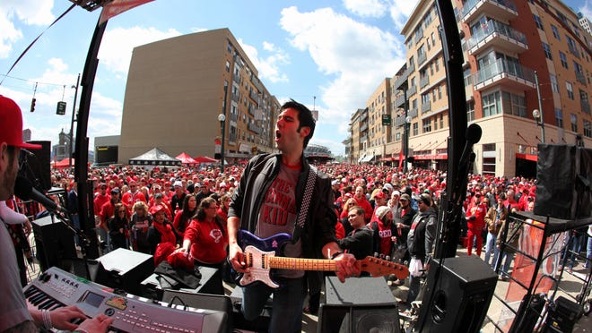 Jesse, lead guitarist with 'Frankly Speaking', entertains a huge crowd during the The Opening Day Block Party in front of the Great American Ballpark. It was the 137th Reds Opening Day. It was shoulder to shoulder as people tried to move through the crowd to reach the various restaurants or just stand in one place to listen to the live music. The Reds were up against the Los Angeles Angels. It was the first interleague Opening Day in Major League Baseball history. Reds Johnny Cueto was the starting pitcher. The game was a sold out.  The photograph was shot with a 15mm lens.  Monday, April 1, 2013 The Enquirer / Liz Dufour