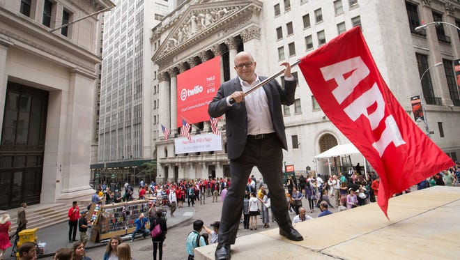 """Jeff Lawson, founder and CEO of cloud communications company Twilio and U-M graduate, hoists a flag with the acronym """"API"""" in front of the New York Stock Exchange on the day of Twilio's IPO in June. """"API"""" stands for """"Application Programming Interface,"""" which are computer programs which form the pipes through which data pass."""
