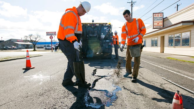 Tanner Helt, left, and Nick Nordlien, right, with the City of Salem seal a pothole with tar and cover the fresh tar with dirt on 12th Street near Waller Street SE on Friday, March 10, 2017. A harsh winter made it challenging to permanently patch many potholes around the city, but crews were out on Friday with asphalt and tar to provide a more permanent fix.