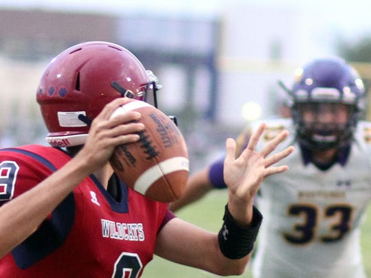 Wildcat quarterback Daniel Garcia attempts a pass against a hard-charging El Paso Burges defense.
