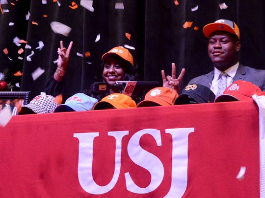 Orange and white confetti falls after University School of Jackson senior lineman Trey Smith (r) was joined on stage with his sister, Ashley, when he made his commitment to The University of Tennessee, Tuesday, Dec. 6.