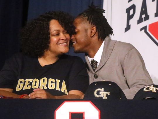 Oakland's Kaleb Oliver, kisses his mother Hope Oliver on the cheek after signing with Georgia Tech on National Signing Day, on Wednesday, Feb. 1, 2017.