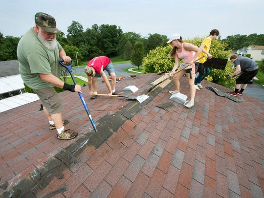 A work group begins scraping shingles off of Norma Kauffman's roof in Monaghan Township. Work crews are volunteering all week, helping people who can't afford labor or materials.