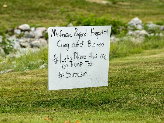 """A homemade sign that reads """"McKenzie Regional Hospital Going out of Business"""" with the hashtag """"Let's Blame this one on Trump Too."""" and #Sarcasm is placed on the property of the McKenzie Medical Center. The hospital will be closing its doors in September of 2018."""