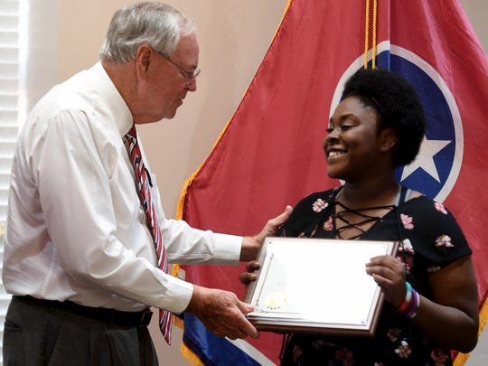 Huntingdon Mayor Dale Kelley presents Huntingdon High School senior Jamontia Compton with an plaque from the city of Huntingdon for her design of the new Dixie Carter Performing Arts and Academic Enrichment Center signage, Tuesday, September 26.