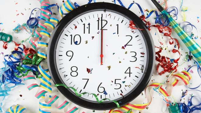 Clock showing midnight surrounded by confetti and ribbons.