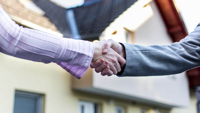 Stock photo of a handshake for buying a house.