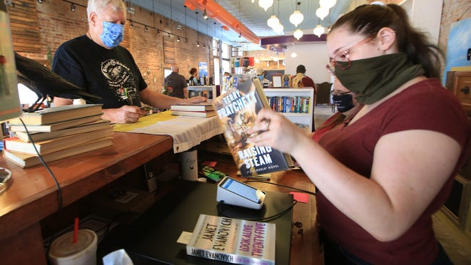 Veda Mansur, right, helps customer Charley McCue with his book purchases Saturday at Crow & Co., 2 South Main. The new independent bookstore held a soft opening on Saturday.