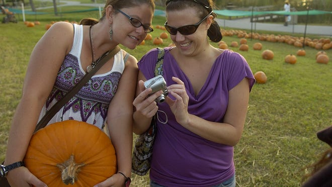 Aubrey Reiter and Abby Cannon check out a picture of themselves at the pumpkin patch at Lakes Park in Fort Myers in 2009.