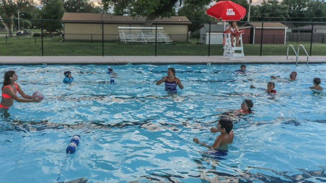 Children play water volleyball during the Back To School Free Swim, sponsored by the Solomon Recreation Commission, on Saturday.  A nearby thunderstorm forced everyone out of the water until the area was deemed clear to re-enter.