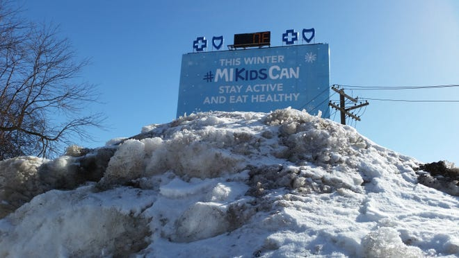 A tower of snow stands in the foreground of a Blue Cross Blue Shield of Michigan billboard promoting the state's child health insurance program and showing a zero degree temperature in Detroit, Sunday, Feb. 15, 2015. Michigan was gripped by a deep Arctic weather system, with low temperatures dropping to -27 at Newberry in the Upper Peninsula and -7 at Detroit.