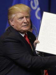 President Donald Trump holds up an executive order to tighten the rules for technology companies seeking to bring highly skilled foreign workers to the U.S. on April 22.