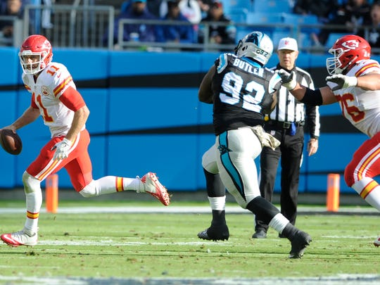 Kansas City Chiefs' Alex Smith (11) scrambles past Carolina Panthers' Vernon Butler (92) in the second half of an NFL football game in Charlotte, N.C., Sunday, Nov. 13, 2016. (AP Photo/Mike McCarn)