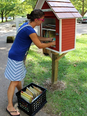 Holly Bennett stocks a little free library with books Monday afternoon at Rising Park in Lancaster.