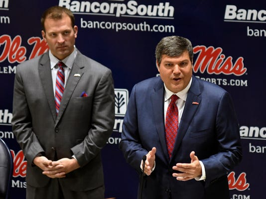 Matt Luke gestures as he speaks after being introduced as the new NCAA college football head coach at the University of Mississippi during a press conference in Oxford, Miss., Monday, Nov. 27, 2017. At left is Mississippi athletic director Ross Bjork. (Bruce Newman, Oxford Eagle via AP)