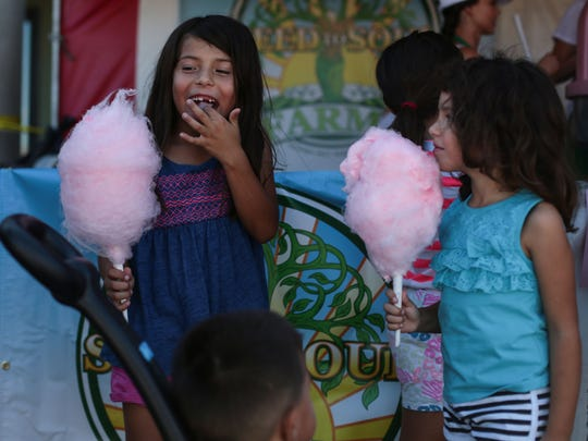 Children eat cotton candy at the fall festiva put on by the Desert Hot Springs Cannabis Alliance Network on Saturday, October 1, 2016 in Desert Hot Springs.
