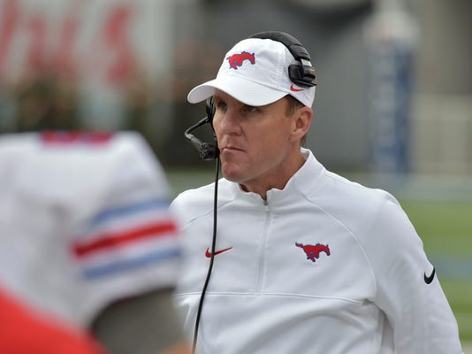 FILE - In this Nov. 18, 2017, file photo, SMU head coach Chad Morris watches from the sideline in the first half of an NCAA college football game against Memphis, in Memphis, Tenn. A person with direct knowledge of the decision tells The Associated Press that Arkansas has hired SMU's Chad Morris to become the school's new football coach. The person spoke Tuesday night, Dec. 5, 2017, on the condition of anonymity because the decision hasn't been made public yet. (AP Photo/Brandon Dill)