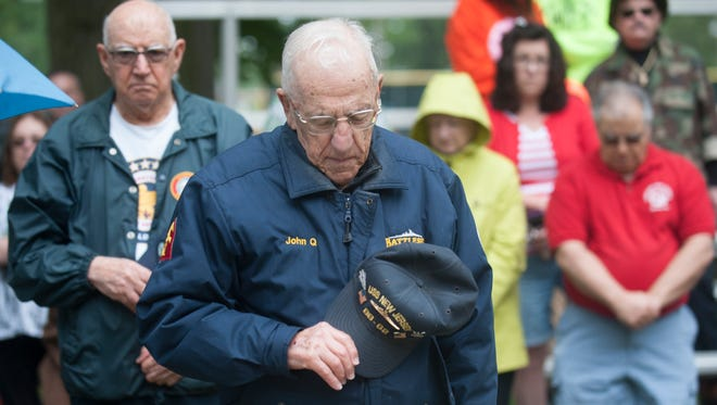 U.S. Navy veteran John Quinesso of Vineland, front, stands for the benediction during Vineland's Memorial Day Service held at Landis Park on Monday.  05.29.17