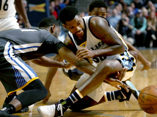 Golden State Warriors Ian Clark and Memphis Grizzlies Troy Daniels get in a tangle for a loose ball.