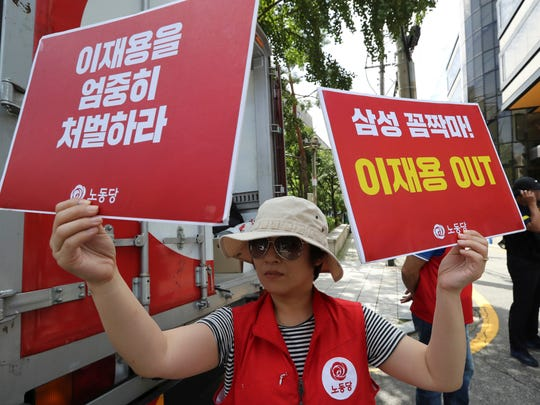 "A protester holds banners reading ""Out, Lee Jae-yong,"""