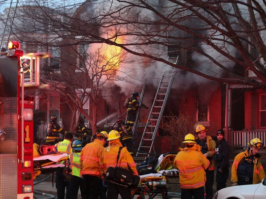 Firefighters work at a house fire in the 400 block of W. 23rd Street in Wilmington, reported before 7:30 pm Sunday.