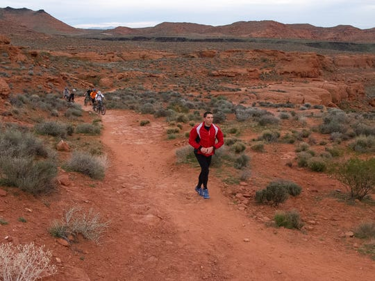 Despite temperatures the 60s, ultra marathoner Cory Reese runs wearing full winter gear, including tights and several layers beneath his running jacket as he runs the Turtle Wall Trail in the Red Cliffs Desert Reserve while training for the Badwater ultra marathon Thursday, March 3, 2016.