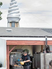 Travis Rost works in the hot outdoor kitchen above the giant ice cream conevat Rost Brothers BBQ & Creamery in Dover Township.