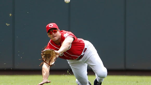 Reds center fielder Chris Heisey dives for a line drive