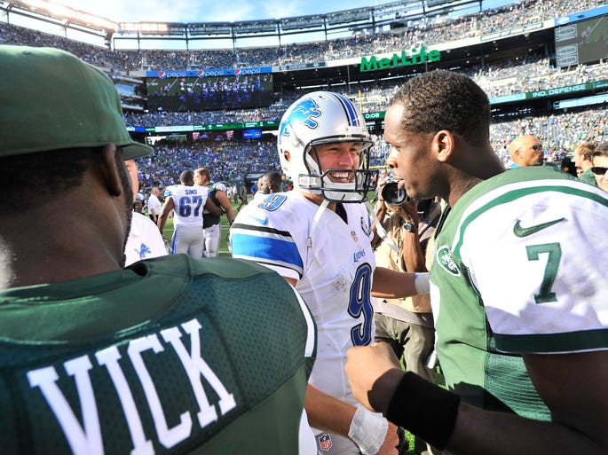 Lions quarterback Matthew Stafford is all smiles after talking with Jets backup quarterback Michael Vick and meeting with starting quarterback Geno Smith after Detroit's 24-17 victory at Metlife Stadium in Rutherford, New Jersey on September 28,2014.