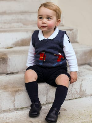 Britain's Prince George poses for a photograph in a courtyard at Kensington Palace, London. Great-grandchild to Britain's Queen Elizabeth II,  Prince George was born July 22, 2013.