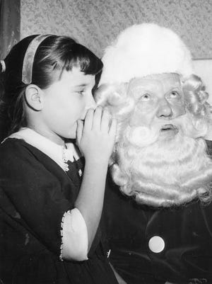 DECEMBER 6, 1960: Santa Is Good Listener. An unidentified girl whispers what she wants for Christmas into Santa Claus's ear at Shillito's.