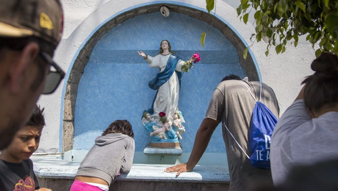 Central American migrants pray with their family outside a church in Puebla, Mexico.
