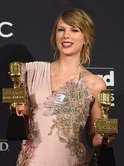 Taylor Swift posa junto sus dos estatuillas.