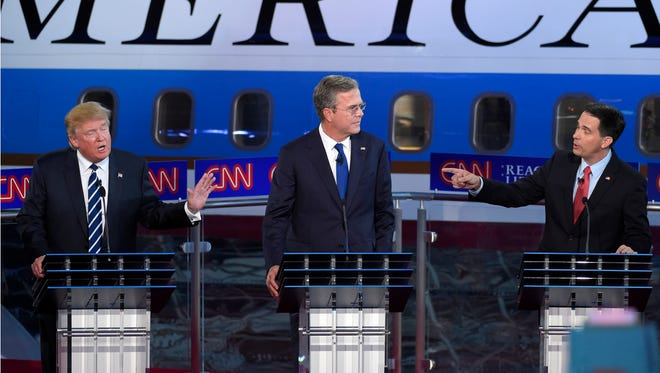 Republican presidential candidates, businessman Donald Trump, left, and Scott Walker, right, both speak as Jeb Bush, looks on during the CNN Republican presidential debate at the Ronald Reagan Presidential Library and Museum on Wednesday, Sept. 16, 2015, in Simi Valley, Calif.
