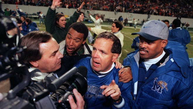 Coach Rip Scherer, center, talks with the media following the Tigers's win over UT at Liberty Bowl Memorial Stadium November 9, 1996. (Steven G. Smith/The Commercial Appeal files)
